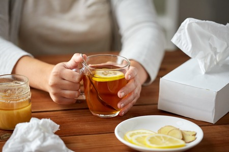health, traditional medicine and ethnoscience concept - close up of ill woman drinking tea with lemon, honey and ginger at wooden table Stock Photo