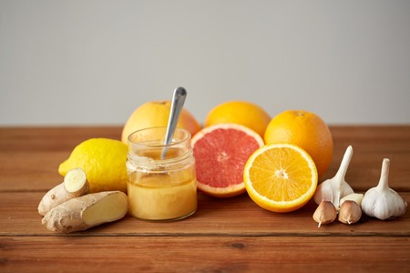 traditional medicine, cooking, food and ethnoscience concept - honey, citrus fruits with ginger and garlic on wooden table