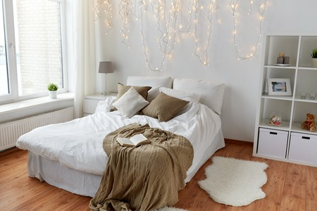coziness: coziness, comfort, interior and holidays concept - cozy bedroom with bed and christmas garland lights at home Stock Photo