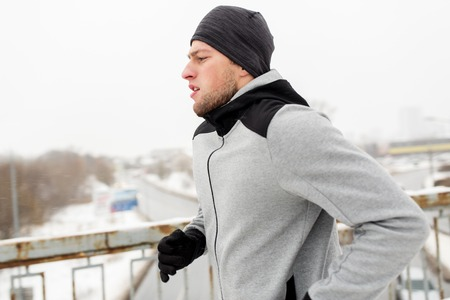 warming up: fitness, sport, people, season and healthy lifestyle concept - young man running along winter bridge