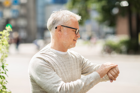 punctuality: punctuality and people concept - senior man checking time on wristwatch or smart watch on his hand in city Stock Photo