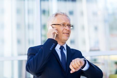 puntualidad: negocios, tecnología, tiempo, la puntualidad y el concepto de la gente - hombre de negocios mayor que invita al teléfono inteligente con reloj de pulsera o reloj inteligente en su mano en la ciudad