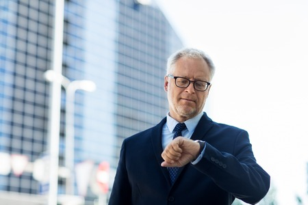 punctuality: business, punctuality and people concept - senior businessman checking time on wristwatch or smart watch on his hand in city Stock Photo
