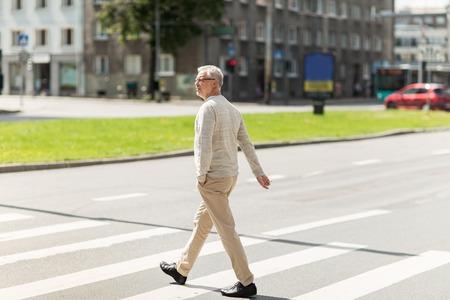 old street: leisure and people concept - senior man walking along summer city crosswalk