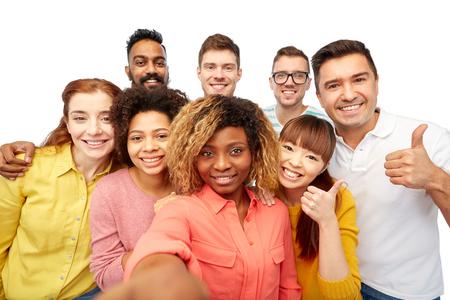 la diversidad, la raza, el origen étnico, la tecnología y el concepto de la gente - grupo internacional de hombres y mujeres sonrientes felices que toman autofoto sobre blanco
