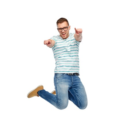 people jumping: La felicidad, la libertad, el movimiento y la gente concepto - feliz joven saltando en el aire y señalando los dedos a usted