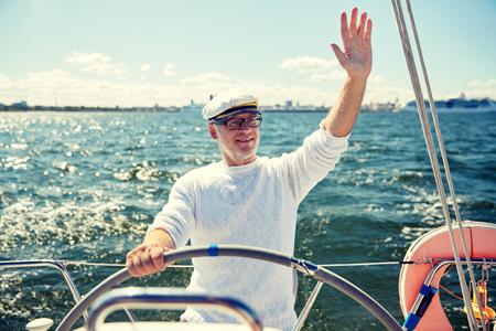 helm boat: la vela, la edad, el turismo, los viajes y el concepto de la gente - hombre mayor feliz en el sombrero de capitán en el volante y agitando la mano barco de vela o yate que flota en el mar