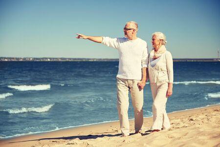 la famille, l'âge, Voyage, tourisme et les gens concept - heureux couple marchant haut et pointant du doigt quelque chose sur la plage d'été