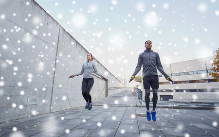 couple exercising: fitness, sport, people, exercising and healthy lifestyle concept - man and woman skipping with jump rope outdoors over snow