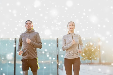 fitness, sport, people, exercising and lifestyle concept - happy couple of sportsmen running in city over snow Stock Photo