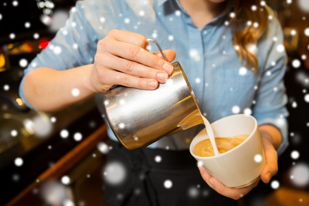 equipment, people and technology concept - close up of woman pouring cream to cup of coffee at cafe bar or restaurant kitchen over snow