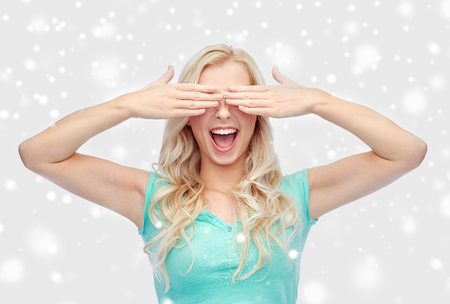 emotions, expressions and people concept - smiling young woman or teenage girl covering her eyes with palms over snow