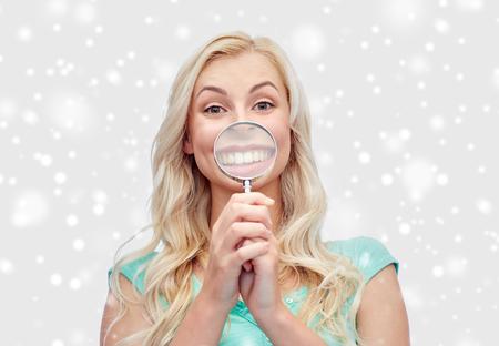 pret, emoties, uitdrukkingen en mensenconcept - gelukkige glimlachende jonge vrouw of tiener die met vergrootglas gezicht over sneeuw maken