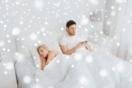 unfaithful: people, technology, cheating, internet addiction and communication concept - man with smartphone texting message while woman is sleeping in bed over snow Stock Photo