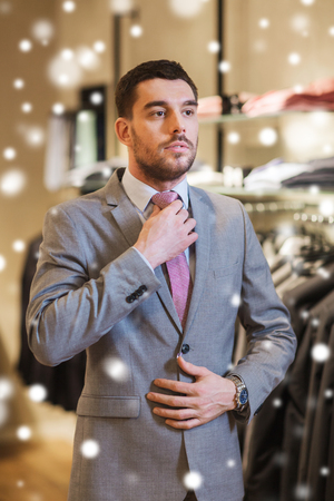 lifestyle shopping: sale, shopping, fashion, business style and people concept - elegant young man choosing and trying on suit and tie in mall or clothing store over snow
