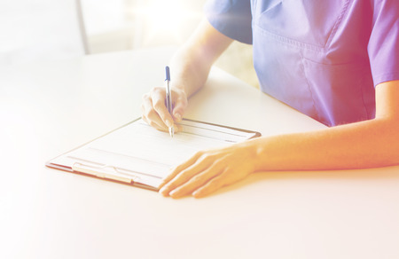 prescribing: medicine, people and healthcare concept - close up of female doctor or nurse writing medical report to clipboard at hospital