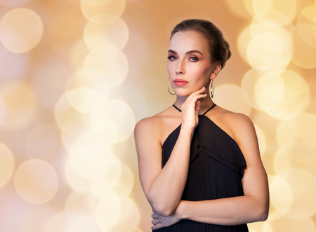 people, luxury, jewelry and fashion concept - beautiful woman in black wearing diamond earrings over beige holidays lights background