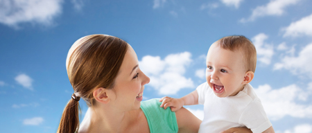 familia, niño y el concepto de la paternidad - feliz madre joven sonriente con el pequeño bebé sobre el cielo azul y las nubes de fondo