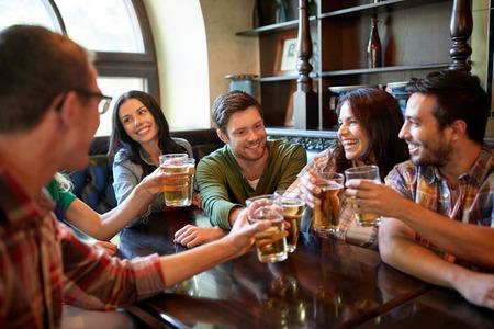 人、レジャー、友情およびお祝いのコンセプト - 幸せな友達を見る飲酒ドラフト ビールとチリンとガラス棒かパブ 写真素材