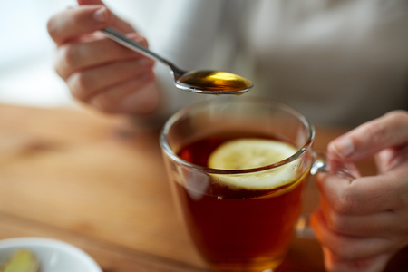 sweetener: healthy food, eating and ethnoscience concept - close up of woman adding honey to tea cup with lemon
