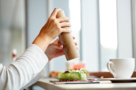 seasoning: food, culinary, eating and people concept - woman hand with salt shaker seasoning brie cheese salad at restaurant or cafe Stock Photo