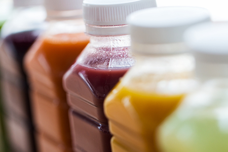 healthy eating, drinks, diet and detox concept - close up of plastic bottles with different fruit or vegetable juices