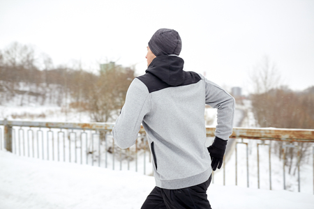 fitness, sport, people, season and healthy lifestyle concept - young man running along snow covered winter bridge road (motion blurred picture)