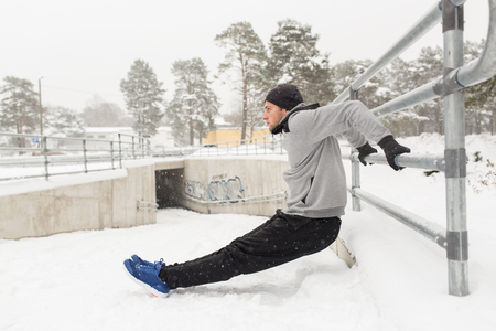 flexing: fitness, sport, people, exercising and healthy lifestyle concept - young man doing triceps dips and warming up at fence in winter Stock Photo