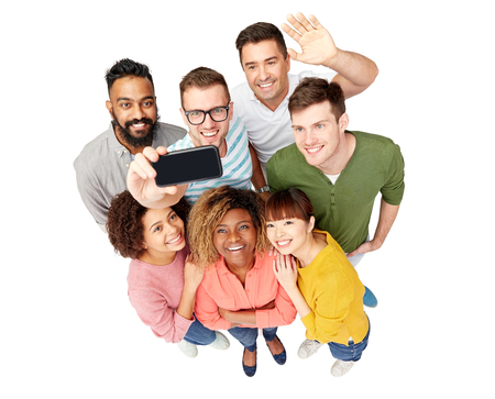 phone isolated: diversity, race, ethnicity, technology and people concept - international group of happy smiling men and women taking selfie by smartphone over white Stock Photo