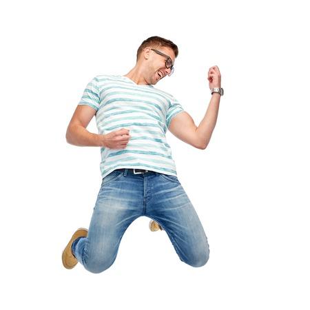 people jumping: movimiento, la diversión y el concepto de la gente - hombre joven y feliz saltando en el aire y tocar la guitarra imaginaria