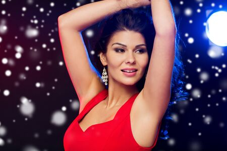 people, winter holidays, disco, night lifestyle and leisure concept - close up of beautiful sexy woman in red dress dancing at nightclub over snow