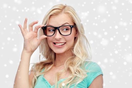 la visión, la educación y el concepto de la gente - Feliz sonriente joven mujer o niña adolescente vasos sobre la nieve Foto de archivo
