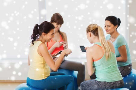 fitball: pregnancy, sport, fitness, people and healthy lifestyle concept - group of happy pregnant women with tablet pc computer and smartphone sitting on balls in gym over snow