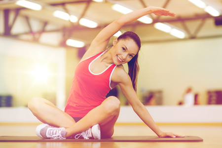hispanic woman: fitness, sport, training, gym and lifestyle concept - smiling woman stretching on mat in the gym Stock Photo