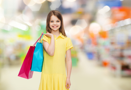 little girl dress: sale, children and people concept - smiling little girl in yellow dress with shopping bags over supermarket background