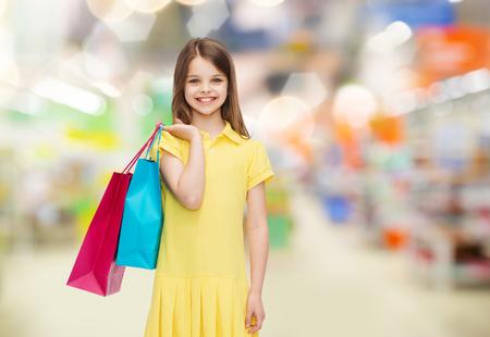 petite fille avec robe: vente, les enfants et les concepts - sourire petite fille en robe jaune avec des sacs sur fond supermarché