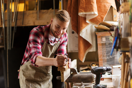 profession, people, carpentry, woodwork and people concept - happy carpenter with jointer planing wood plank at workshop Standard-Bild