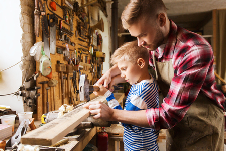 hammering: family, carpentry, woodwork and people concept - father and little son with hammer hammering nail into wood plank at workshop
