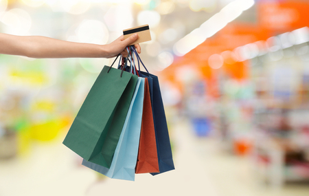 people, consumerism, finances and sale concept - hand with shopping bags and credit card over supermarket background Stock Photo
