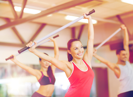 fitness, sport, training, gym and lifestyle concept - group of smiling people working out with barbells in the gym Stock Photo