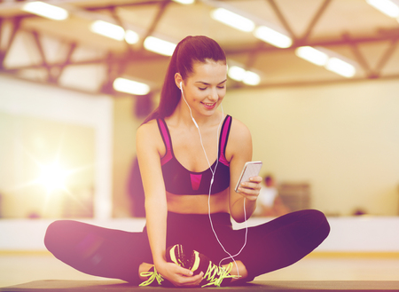 fitness, sport, training, gym, technology and lifestyle concept - smiling woman with smartphone Stock Photo