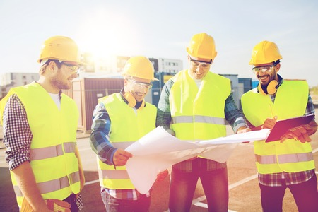 happy workers: business, building, teamwork and people concept - group of smiling builders in hardhats with clipboard and blueprint outdoors