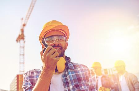 건설 현장에서 휴대용 무선 전화기, 라디오와 안전모의 산업, 건물, 기술과 사람들 개념 - 남성 빌더