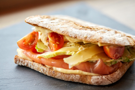 panino: food, dinner and eating concept - salmon panini sandwich with tomatoes and cheese on stone plate at restaurant