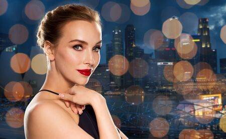 femme fatale: people, luxury and fashion concept - beautiful woman in black with red lips over singapore city and holidays lights background