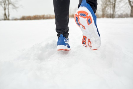 fitness, sport, people, footwear and healthy lifestyle concept - close up of male feet running along winter road and snow Stock Photo