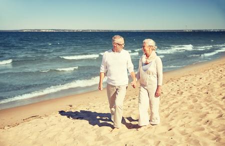 viaje familia: familiar, la edad, los viajes, el turismo y el concepto de la gente - feliz pareja mayor que recorre a lo largo de la playa del verano Foto de archivo