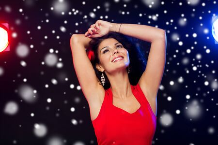 people, winter holidays, disco, night lifestyle and leisure concept - beautiful sexy woman in red dress dancing at nightclub over snow Stock Photo