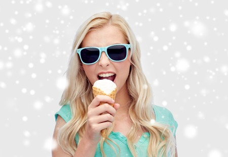 winter holidays, junk food and people concept - young woman or teenage girl in sunglasses eating ice cream over snow