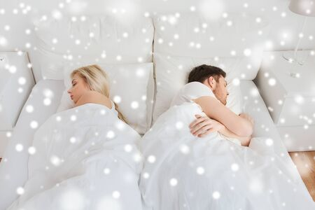lovers quarrel: people, relationship difficulties, conflict and family concept - couple sleeping in bed at home over snow Stock Photo